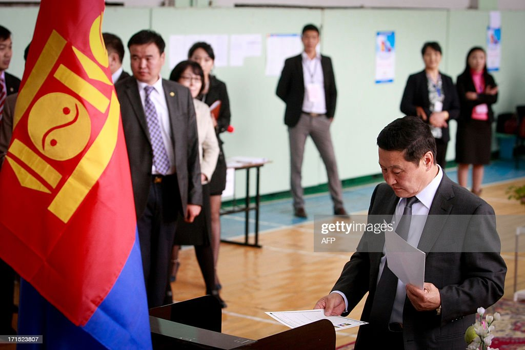 Mongolian Prime Minister Norov Altankhuyag (Bottom R) votes at a polling station during presidential elections in Ulan Bator on June 26, 2013. Mongolians voted on June 26 in a presidential election pitting the front-running incumbent against a champion wrestler and a woman, amid calls for a fairer distribution of the former Soviet satellite's spectacular mining wealth. AFP PHOTO/ BYAMBASUREN BYAMBA-OCHIR