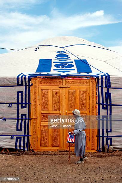 Mongolian shopper passes by a traditional 'ger' nomadic dwelling outside Gandan Monastery unashamedly clutching her starsandstripes shopping bag