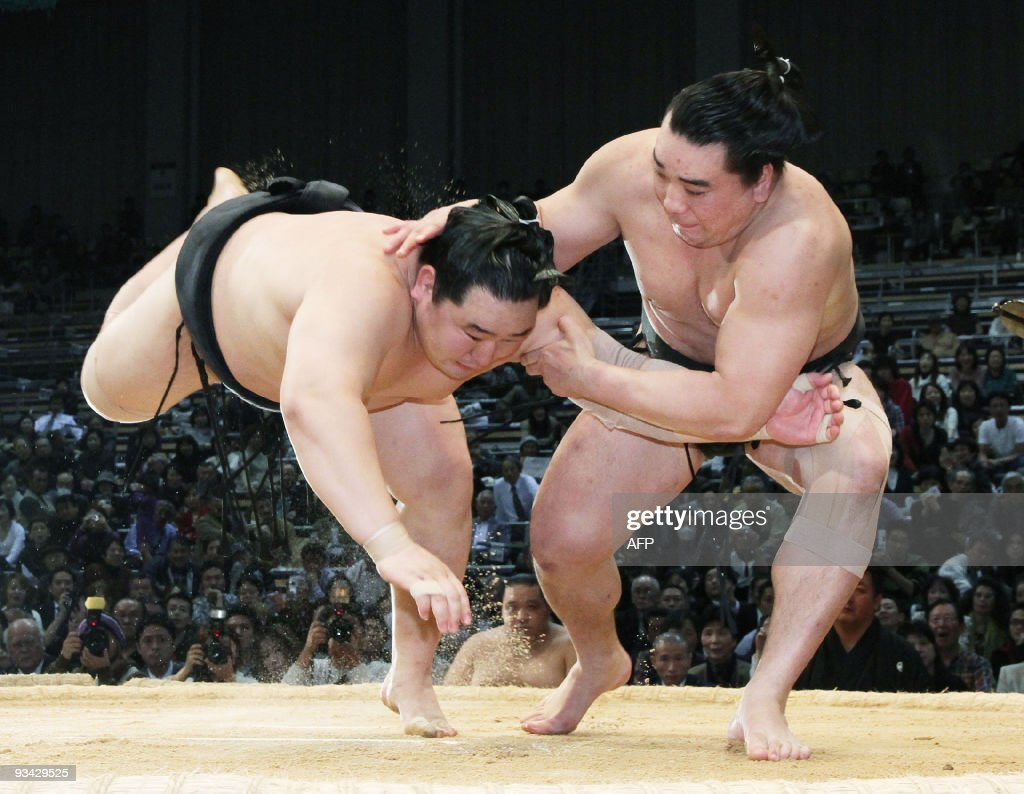 Mongolian sumo grand champion Asashoryu is thrusted down in the ring by his compatriot Harumafuji during a 12th day bout of the Kyushu Grand Sumo...