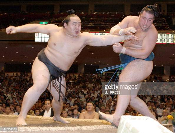 Mongolian sumo grand champion Asashoryu pushes Tochinoshin of Georgia out of the ring during the second day of the 15day Autumn Grand Sumo Tournament...
