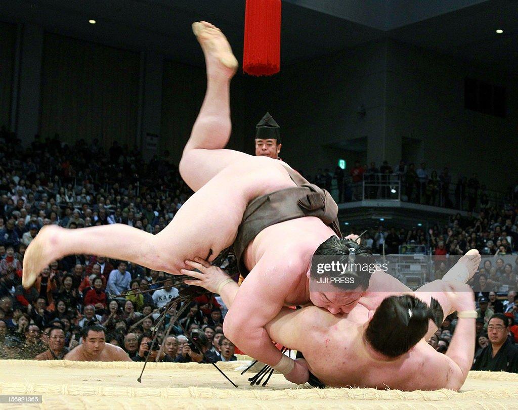 Mongolian sumo grand champion, or 'yokozuna', Hakuho (top) throws down his compatriot and fellow yokozuna Harumafuji (bottom) to the ground to win the bout on the last day of the 15-day Kyushu Grand Sumo Tournament in Fukuoka, on Japan's southern island of Kyushu on November 25, 2012. Hakuho defeated Harumafuji on the last day to finish with a winning 14-1 record in the 15-day tournament. JAPAN
