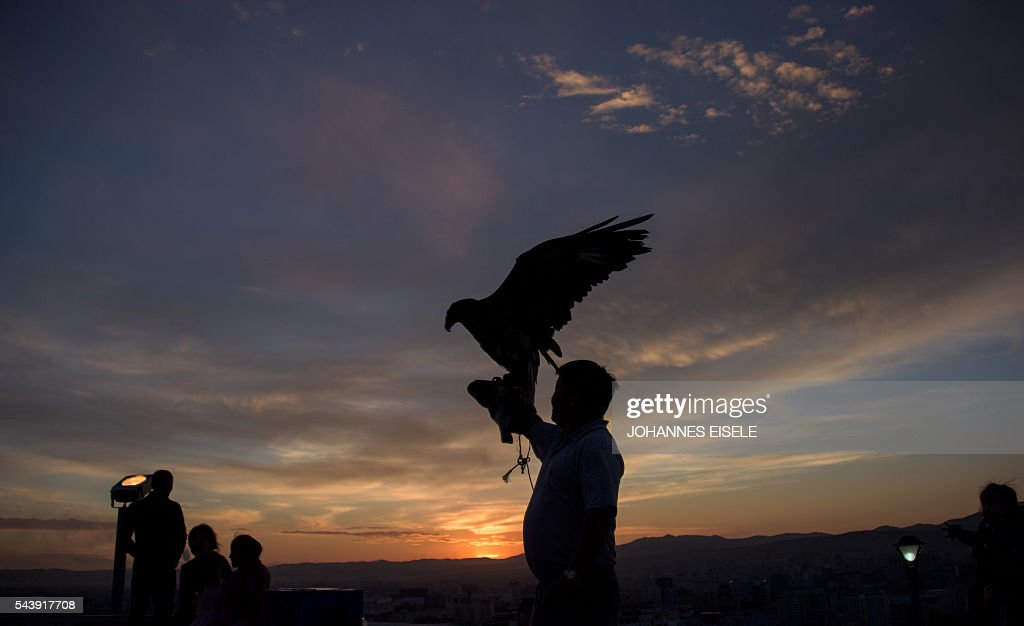 A Mongolian tourist poses with an eagle overlooking Ulan Bator on June 30, 2016. A landslide election victory by Mongolia's opposition is a stinging rejection of the government's failed economic policies, analysts and voters said, as the country struggles to turn its vast natural resources into national wealth. The Mongolian People's Party (MPP) won 65 out of 76 seats in the State Great Hural parliament. / AFP / JOHANNES