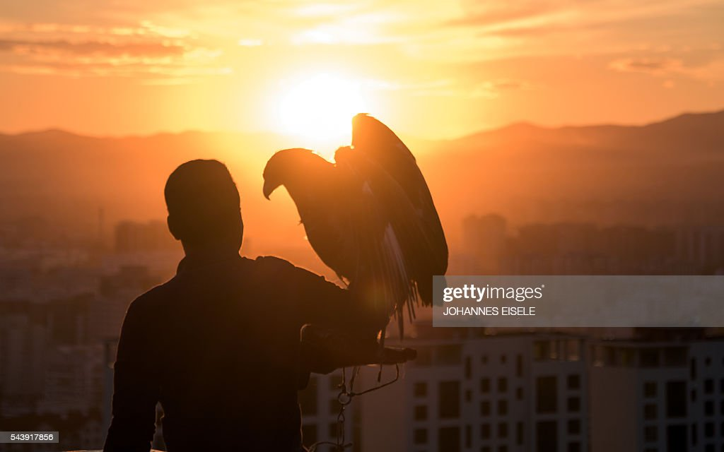 A Mongolian tourist poses with an eagle overlooking Ulan Bator on June 30, 2016. A landslide election victory by Mongolia's opposition is a stinging rejection of the government's failed economic policies, analysts and voters said, as the country struggles to turn its vast natural resources into national wealth. / AFP / JOHANNES