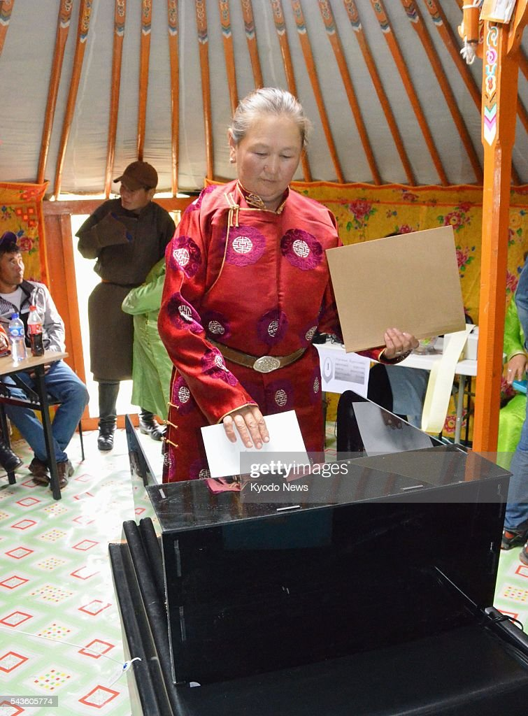 A Mongolian woman casts her ballot for the country's general election in a yurt being used as a temporary polling station in Tov Province, near Ulan Bator, on June 29, 2016.
