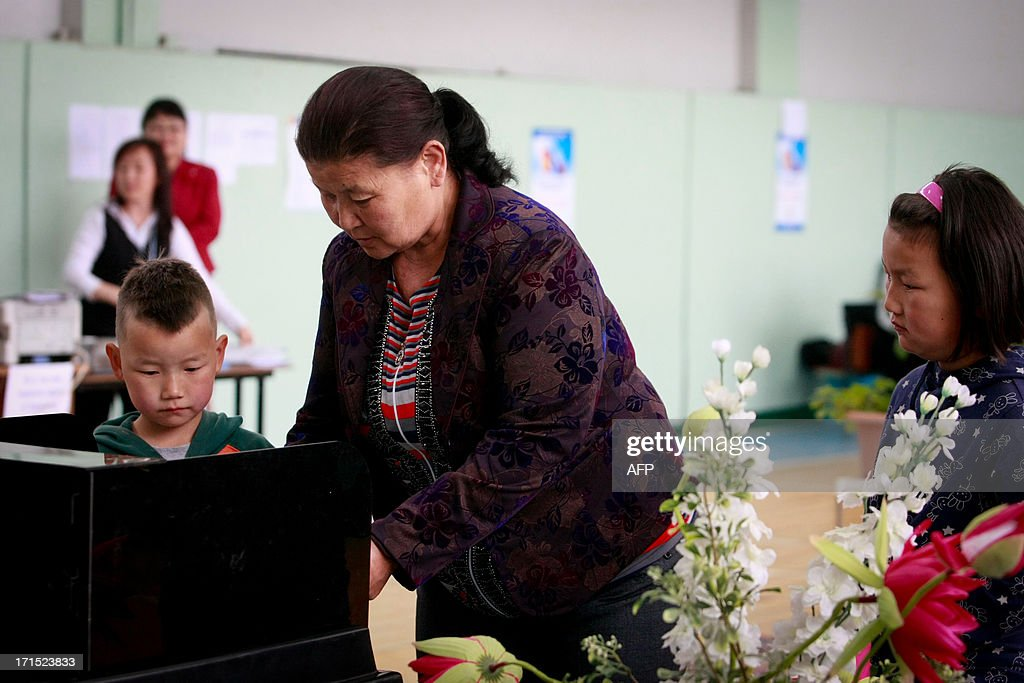 A Mongolian woman (C) casts her ballot into the box at a polling station during presidential elections in Ulan Bator on June 26, 2013. Mongolians voted on June 26 in a presidential election pitting the front-running incumbent against a champion wrestler and a woman, amid calls for a fairer distribution of the former Soviet satellite's spectacular mining wealth. AFP PHOTO/ BYAMBASUREN BYAMBA-OCHIR