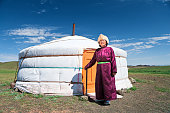 Mongolian woman in national clothing standing next to ger