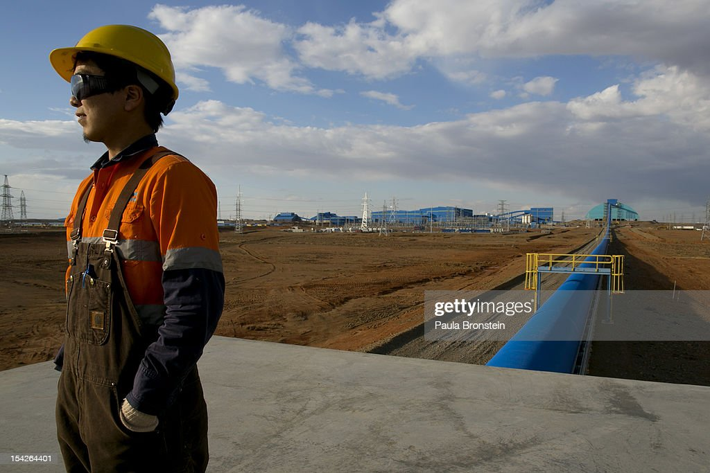 Mongolian worker looks out from operations along the blue conveyor belt that moves rock from the crusher to the concentrator area at the Oyu Tolgoi mine October 11, 2012 in the south Gobi desert, Khanbogd region, Mongolia. The Oyu Tolgoi (Mongolian for Turquoise Hill) copper and gold mine is a combined open pit and underground mining project. The site, discovered in 2001, is located approximately 550 km south of the Mongolian capital, Ulan-Batar in the South Gobi Desert. Turquoise Hill Resources (Formerly Ivanhoe Mines) and Rio Tinto signed a long-term comprehensive investment agreement with the Government of Mongolia in 2009 with the deal awarding Turquoise Hill Resources, whose majority shareholder is Rio Tinto, with a controlling 66 percent interest and The Mongolian Government with a 34 percent interest in the project. Rio Tinto provided a comprehensive financing package and assumed direct management of the project under an agreement with Ivanhoe Mines. Initial production from open pit mining is currently underway and commercial production is planned to start in first half of 2013. An 85million USD investment was earmarked for education and training projects, with Mongolians expected to constitute 90 percent of the work force when production begins in 2013. When Oyu Tolgoi starts fully operating Mongolia will be set to become one of the world's top copper and gold producers with production estimates of 450,000 tons of copper and 330,000 ounces of gold annually. Mongolia is currently the world's fastest growing economy with its GDP increasing by more than 17 percent last year and an estimated $1.3 trillion in untapped mineral resources. Oyu Tolgoi is Mongolia's largest foreign investment project and the country's biggest economic undertaking to date, which is projected to add one-third of future value to the country's GDP by 2020.