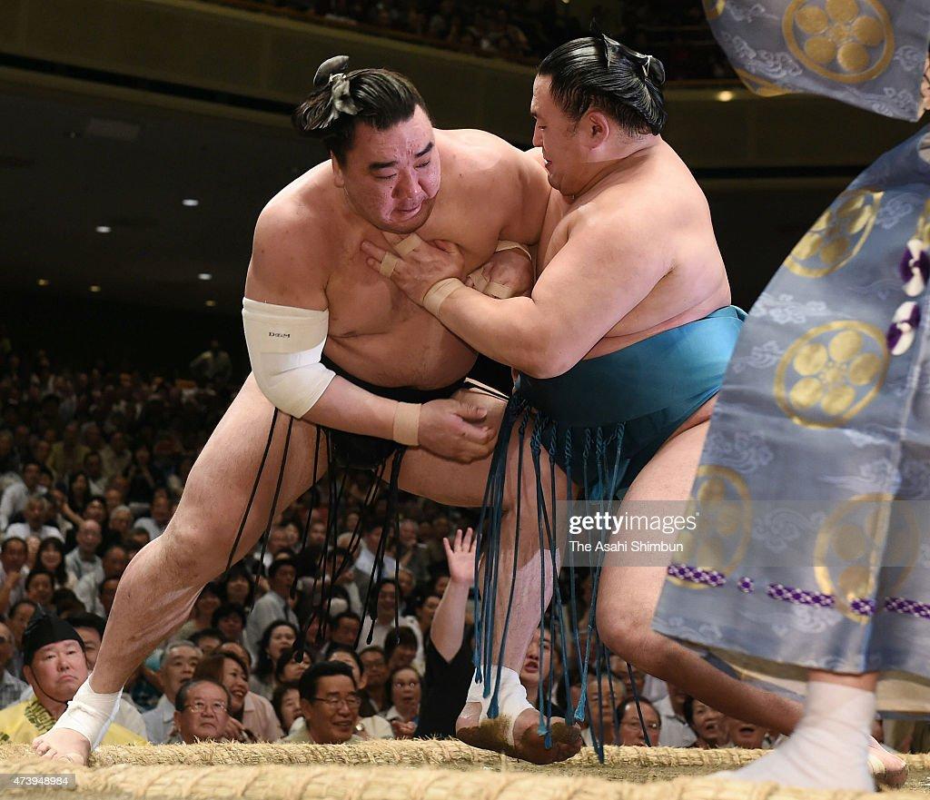 Mongolian wrestler Tamawashi pushes his fellow yokozuna Harumafuji to win during day nine of the Grand Sumo Summer Tournament at Ryogoku Kokugikan on...