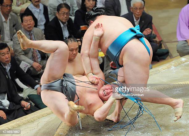Mongolian wrestler Tamawashi throws his fellow wrestler Arawashi to win during day fifteen of the Grand Sumo Summer Tournament at Ryogoku Kokugikan...