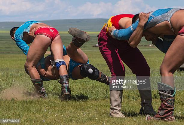 Mongolian wrestlers compete during the traditionnal Nadaam festival in the Ovorkhangai province on July 18 2016 / AFP / JOEL SAGET