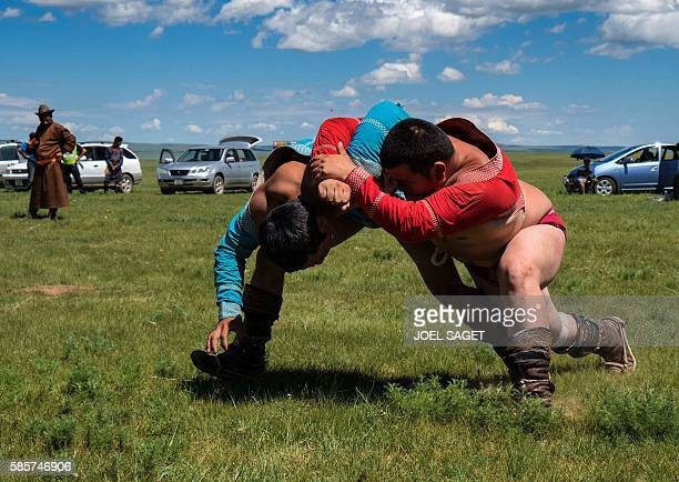 Mongolian wrestlers compete during the traditionnal Nadaam festival in the Ovorkhangai province on July 17 2016 / AFP / JOEL SAGET