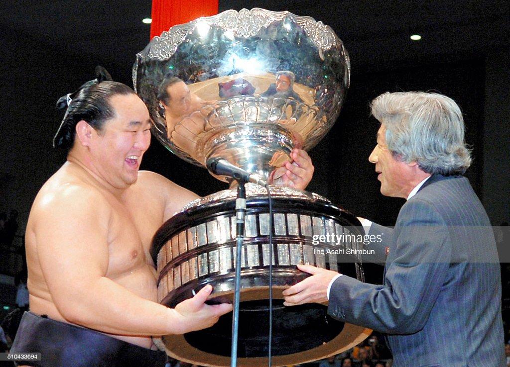 Mongolian yokozuna Asashoryu receives the trophy from Prime Minister Junichiro Koizumi after winning the Grand Sumo Kyushu Tournament at the Fukuoka...