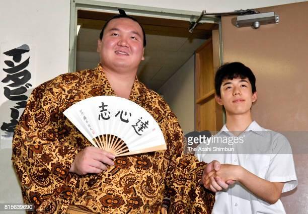 Mongolian yokozuna Hakuho and 14yearold professional shogi player Sota Fujii shake hands after day four of the Grand Sumo Nagoya Torunament at Aichi...