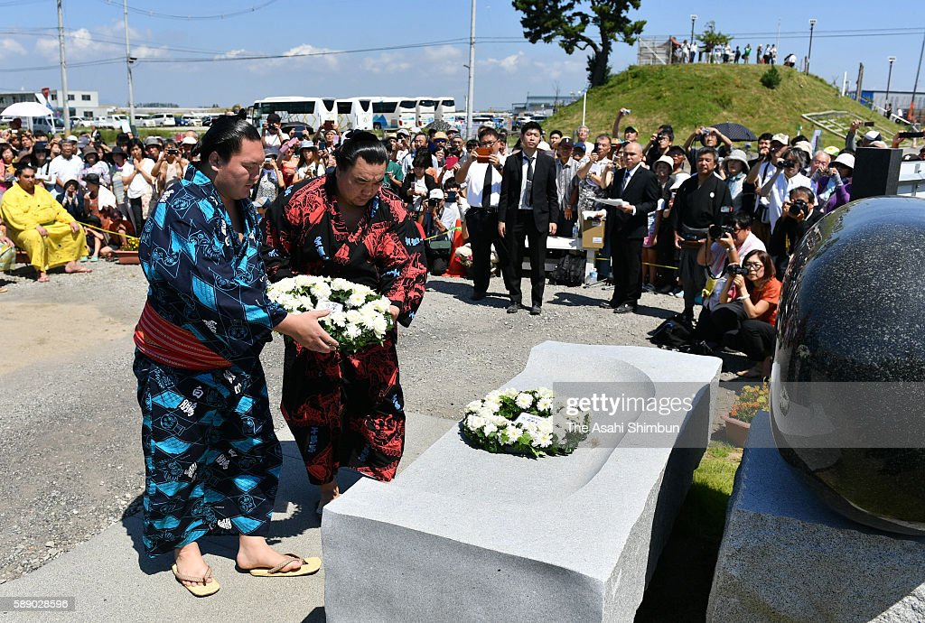 Mongolian yokozuna Hakuho and Harumafuji offer a wreath before performing the 'DohyoIri' ring purification ritual in front of the memorial in pray...