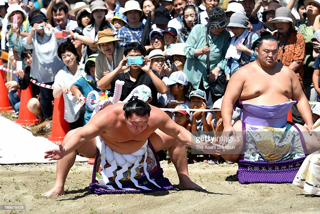 Mongolian yokozuna Hakuho performs the 'DohyoIri' ring purification ritual in front of the memorial in pray for the restoration at Yuriage area where...