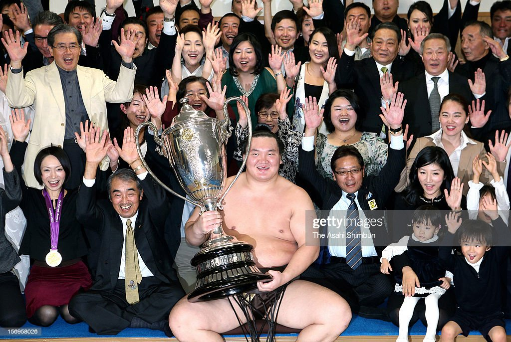 Mongolian yokozuna <a gi-track='captionPersonalityLinkClicked' href=/galleries/search?phrase=Hakuho&family=editorial&specificpeople=625611 ng-click='$event.stopPropagation()'>Hakuho</a> poses for photographs with his supporters after winning the Grand Sumo November Tournament at Fukuoka Convention Center on November 25, 2012 in Fukuoka, Japan.