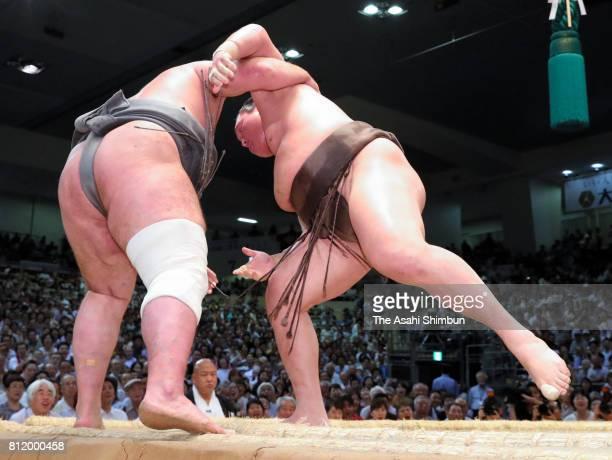 Mongolian yokozuna Hakuho pushes Georgian wrestler Tochinoshin out of the ring to win during day two of the Grand Sumo Nagoya Torunament at Aichi...