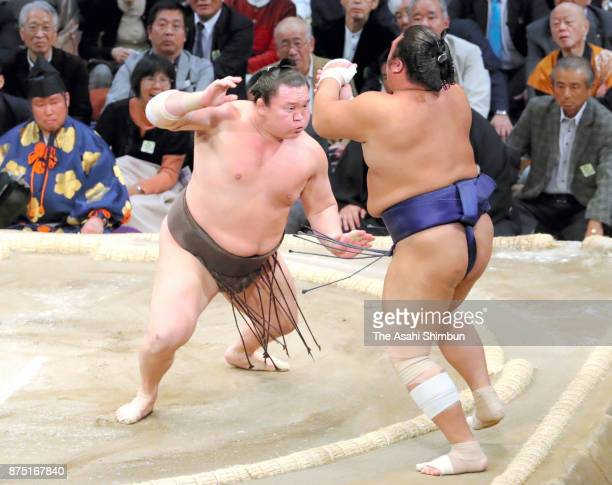 Mongolian yokozuna Hakuho pushes Tochiozan out of the ring to win during day five of the Grand Sumo Kyushu Tournament at Fukuoka Convention Center on...