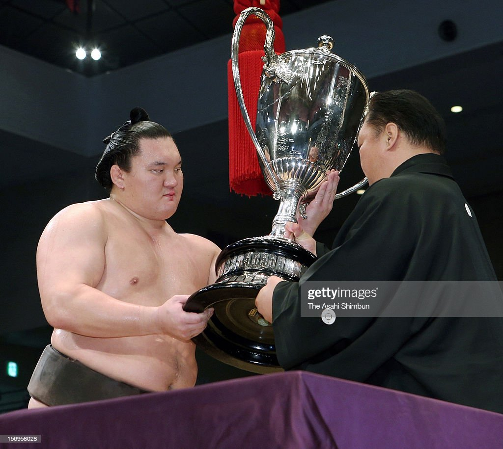 Mongolian yokozuna Hakuho (L) receives the Emperor's Cup from Japan Sumo Association chief Kitanoumi after winning the Grand Sumo November Tournament at Fukuoka Convention Center on November 25, 2012 in Fukuoka, Japan.
