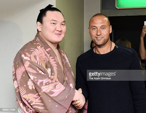Mongolian yokozuna Hakuho shakes hands with former MLB player Derek Jeter after day twelve of the Grand Sumo Spring Tournament at Bodymaker Colosseum...