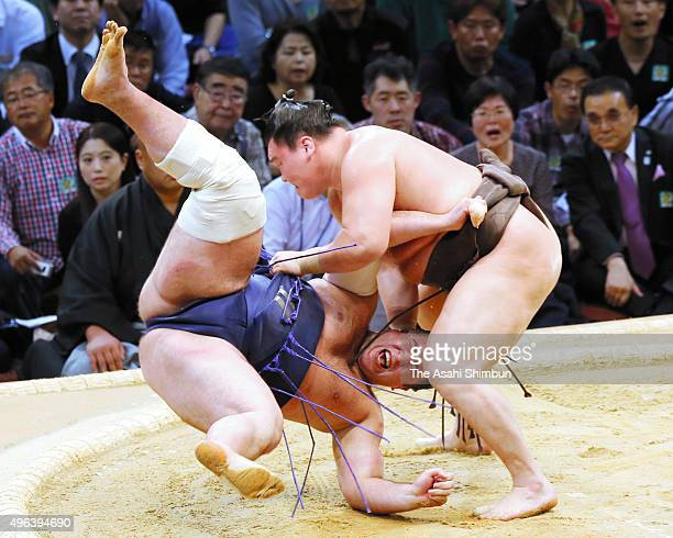 Mongolian yokozuna Hakuho throws Georgian wrestler Tochinoshin during day one of the Grand Sumo Kyushu Tournament at Fukuoka Covention Center on...