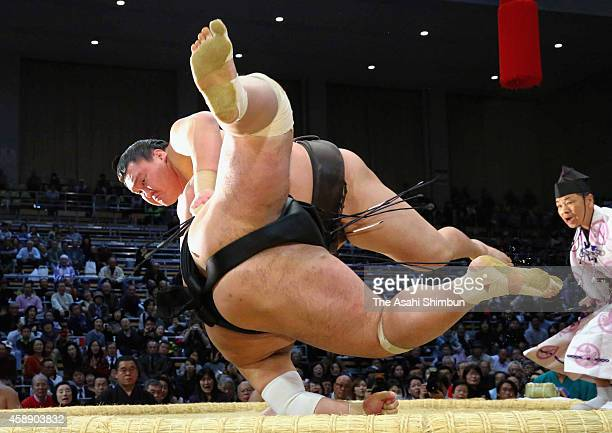 Mongolian yokozuna Hakuho throws Toyohibiki to win during day five of the Grand Sumo Kyushu Tournament at Fukuoka Covention Center on November 13...