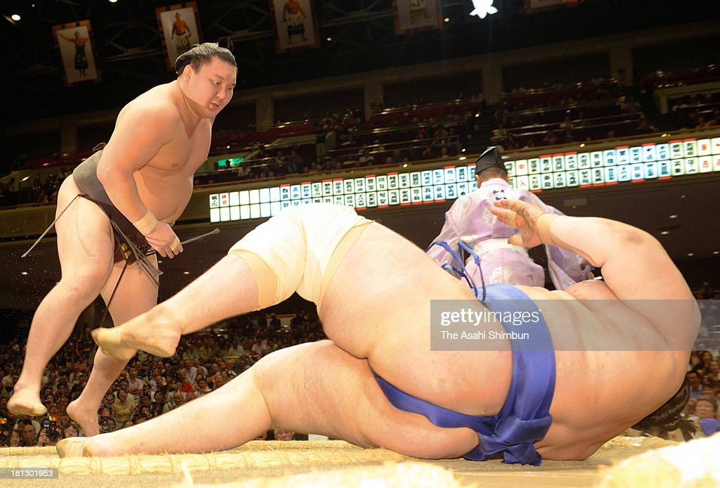 Mongolian yokozuna <a gi-track='captionPersonalityLinkClicked' href=/galleries/search?phrase=Hakuho&family=editorial&specificpeople=625611 ng-click='$event.stopPropagation()'>Hakuho</a> (L), whose real name is Mnkhbatyn Davaajargal throws Bulgarian wrestler Aoiyama, whose real name is Daniel Ivanov during day five of the Grand Sumo Autumn Tournament at Ryogoku Kokugikan on September 19, 2013 in Tokyo, Japan.