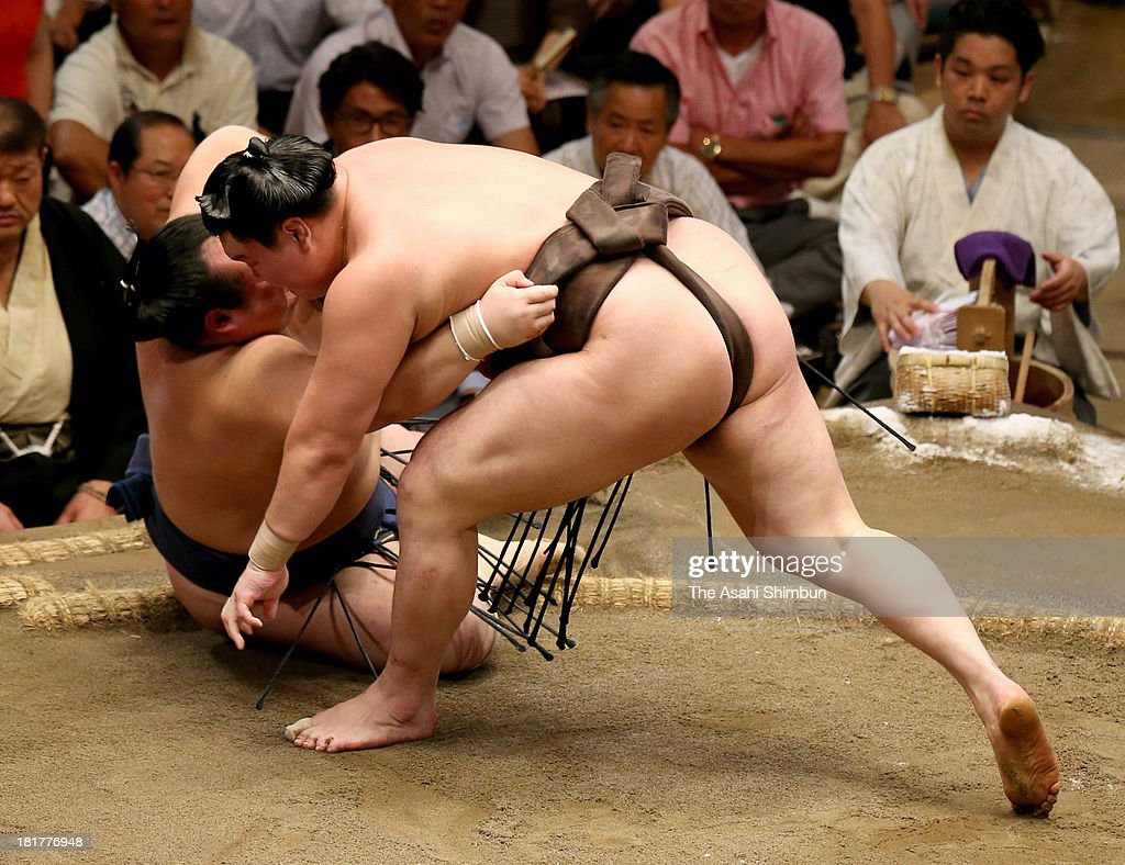 Mongolian yokozuna Hakuho (L), whose real name is Mnkhbatyn Davaajargal throws Takarafuji to win during day eight of the Grand Sumo Autumn Tournament at Ryogoku Kokugikan on September 22, 2013 in Tokyo, Japan.