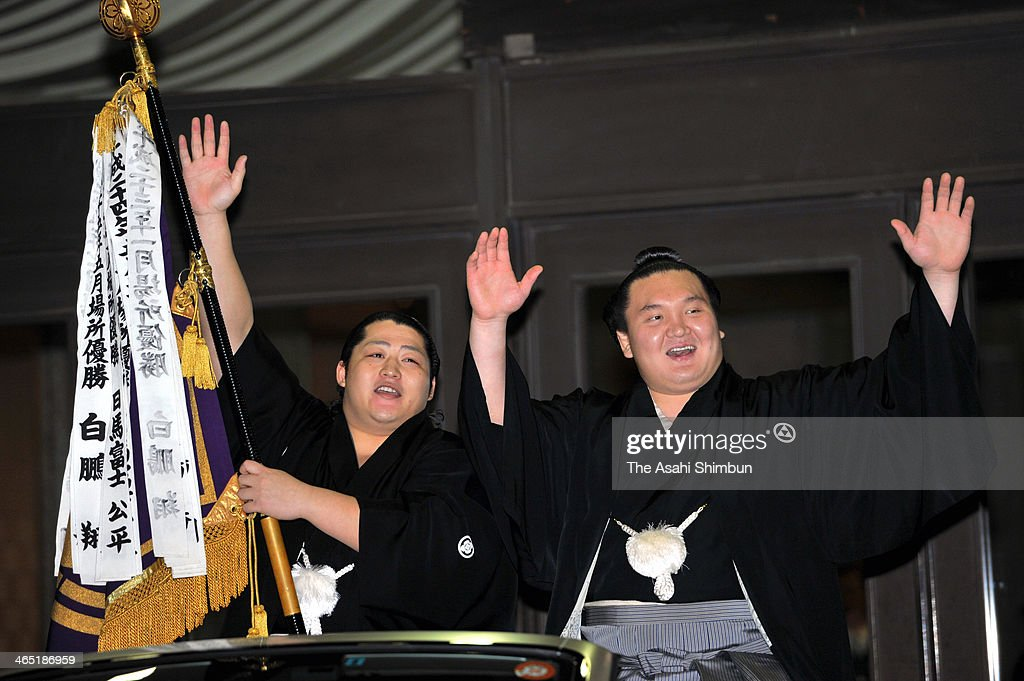Mongolian yokozuna <a gi-track='captionPersonalityLinkClicked' href=/galleries/search?phrase=Hakuho&family=editorial&specificpeople=625611 ng-click='$event.stopPropagation()'>Hakuho</a> (R), whose real name is Munkhbat Davaajargal celebrates during the winning parade after day fifteen of the Grand Sumo New Year Tournament at Ryogoku Kokugikan on January 26, 2014 in Tokyo, Japan.