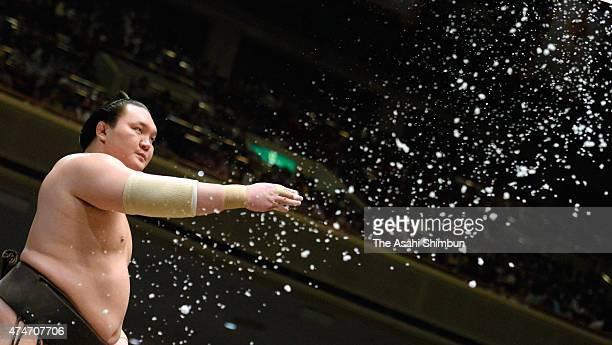 Mongolian yokozuna Haoku splashes a handful of salt before his bout during day fourteen of the Grand Sumo Summer Tournament at Ryogoku Kokugikan on...