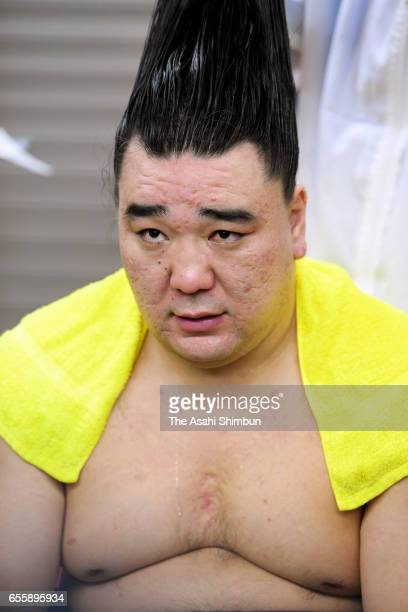 Mongolian yokozuna Harumafuji answers questions from reporters while having his topknot done after his defeat by Arawashi in the dressing room during...