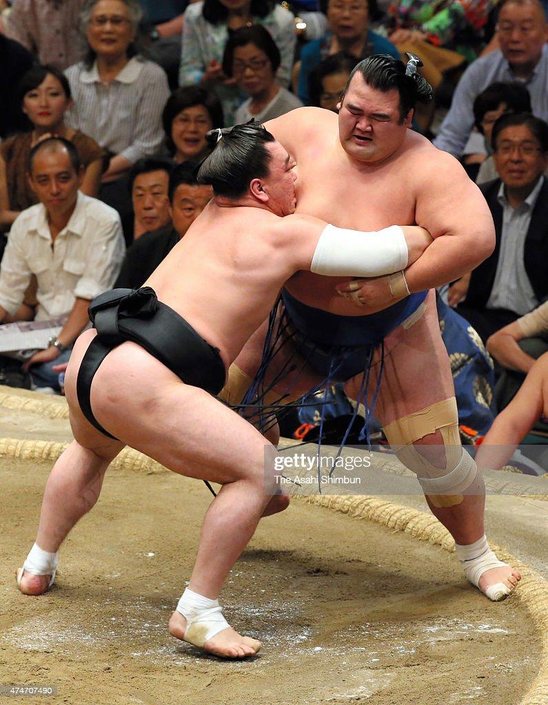 Mongolian yokozuna Harumafuji pushes ozeki Kotoshogiku out of the ring to win during day fourteen of the Grand Sumo Summer Tournament at Ryogoku...