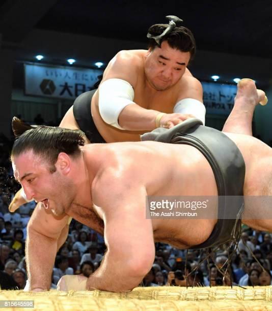 Mongolian yokozuna Harumafuji throws Georgian wrestler Tochinoshin to win during day four of the Grand Sumo Nagoya Torunament at Aichi Prefecture...
