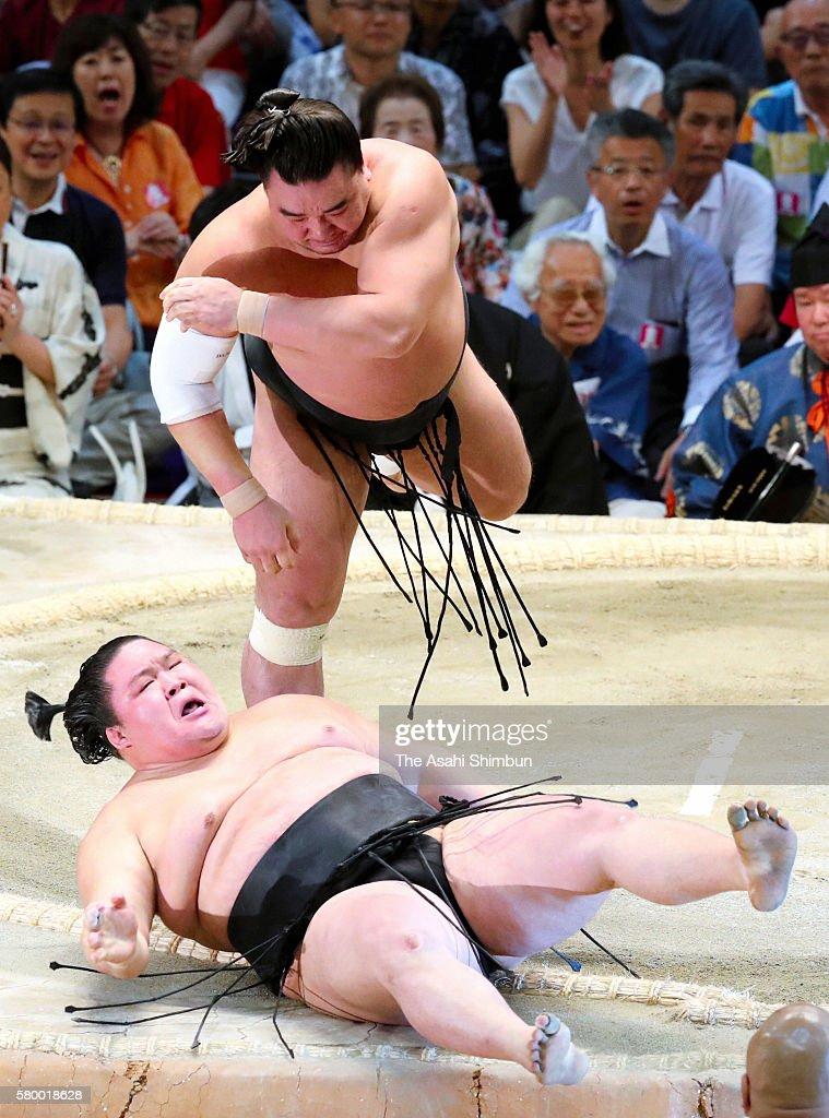 Mongolian yokozuna Harumafuji throws ozeki Goeido to win during day fourteen of the Grand Sumo Nagoya Tournament at the Aichi Prefecture Gymnasium on...
