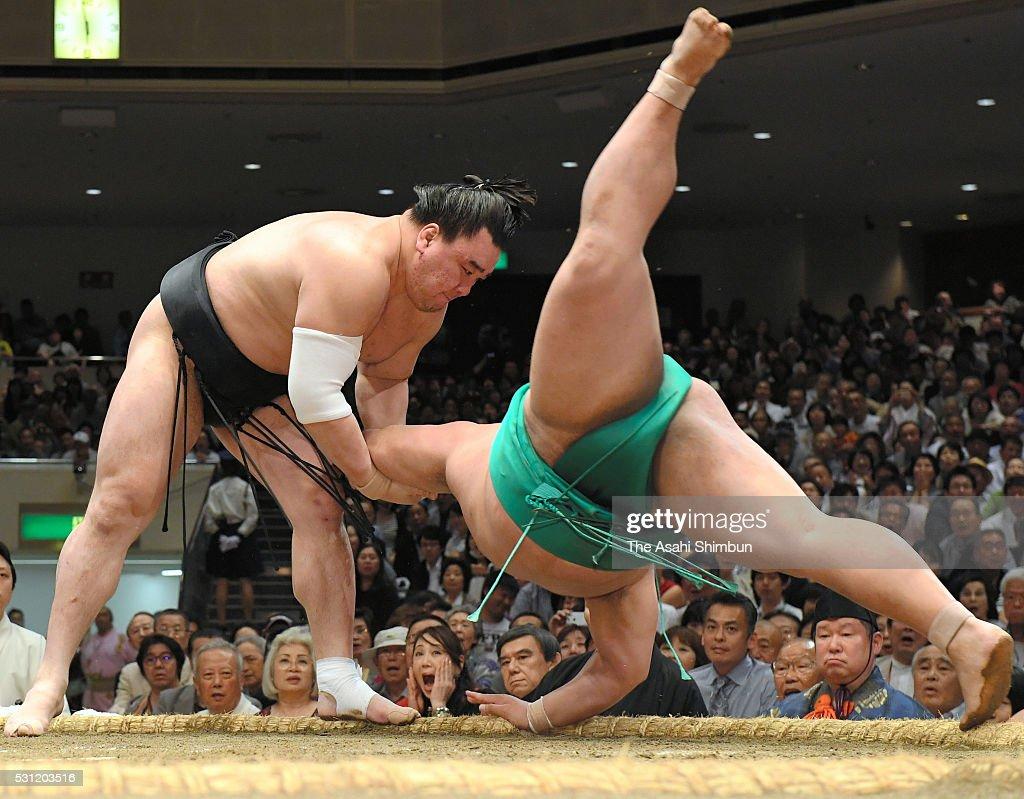 Mongolian yokozuna Harumafuji throws Yoshikaze to win during day six of the Grand Sumo Summer Tournament at Ryogoku Kokugikan on May 13 2016 in Tokyo...