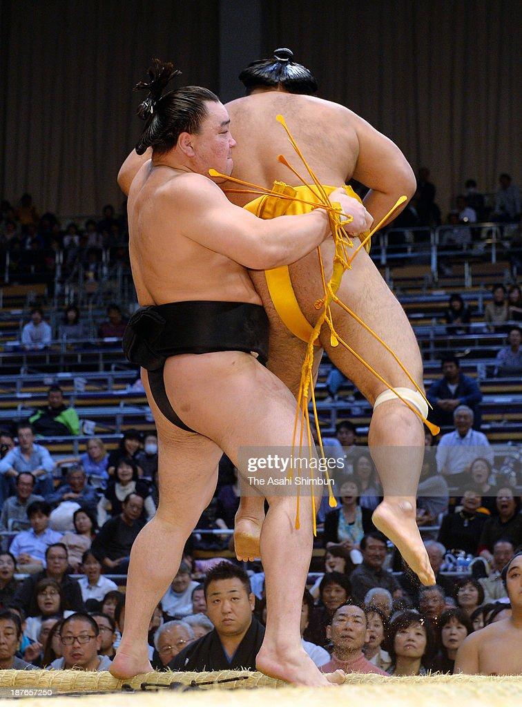 Mongolian yokozuna Harumafuji (L), whose real name is Altangadasyn Khuchitbaatar pulls out Shohozan to win during day one of the Grand Sumo Kyushu Tournament at Fukuoka Convention Center on November 10, 2013 in Fukuoka, Japan.