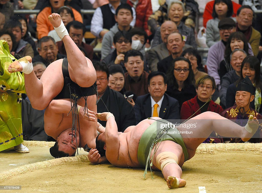 Mongolian yokozuna Harumafuji (L), whose real name is Altangadasyn Khuchitbaatar throws Toyonoshima to win during day one of the Grand Sumo Spring Tournament at Body Maker Colosseum on March 9, 2014 in Osaka, Japan.