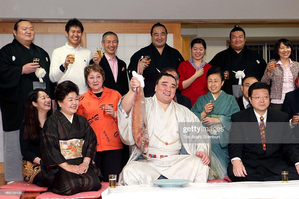 Mongolian yokozuna Harumafuji whose real name is Davaanyamyn Byambadorj raises a sea bream to celebrate winning the Grand Sumo New Year Tournament at...