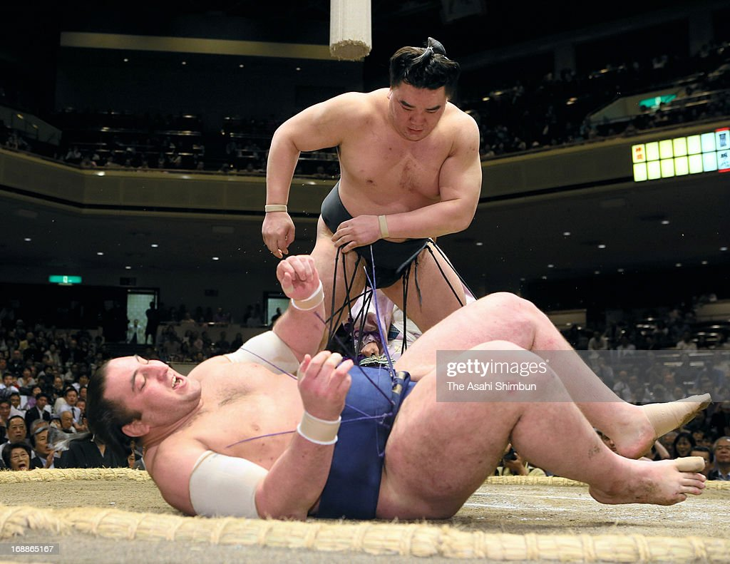Mongolian yokozuna Harumafuji (back), whose real name is Davaanyamyn Byambadorj throws Georgian wrestler Tochinoshin, whose real name is Levan Gorgadze to win during day four of the Grand Sumo Summer tournament at Ryogoku Kokugikan on May 15, 2013 in Tokyo, Japan.