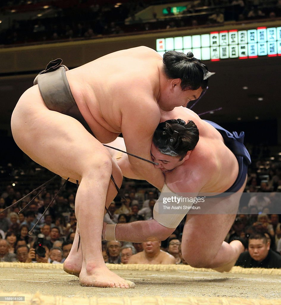 Mongolian Yokozuna, sumo's grand champion <a gi-track='captionPersonalityLinkClicked' href=/galleries/search?phrase=Hakuho&family=editorial&specificpeople=625611 ng-click='$event.stopPropagation()'>Hakuho</a> (L), whose real name is Mnkhbatyn Davaajargal throws Georgian wrestler Tochinoshin, whose real name is Levan Gorgadze to win during day five of the Grand Sumo Summer tournament at Ryogoku Kokugikan on May 16, 2013 in Tokyo, Japan.