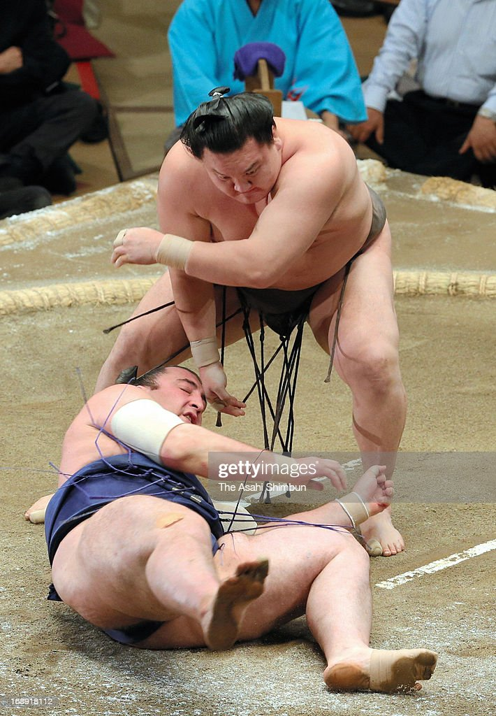 Mongolian Yokozuna, sumo's grand champion <a gi-track='captionPersonalityLinkClicked' href=/galleries/search?phrase=Hakuho&family=editorial&specificpeople=625611 ng-click='$event.stopPropagation()'>Hakuho</a> (top), whose real name is Mnkhbatyn Davaajargal throws Georgian wrestler Tochinoshin, whose real name is Levan Gorgadze to win during day five of the Grand Sumo Summer tournament at Ryogoku Kokugikan on May 16, 2013 in Tokyo, Japan.