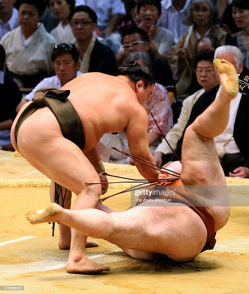 Mongolian Yokozuna, sumo's grand champion <a gi-track='captionPersonalityLinkClicked' href=/galleries/search?phrase=Hakuho&family=editorial&specificpeople=625611 ng-click='$event.stopPropagation()'>Hakuho</a>, whose real name is Mnkhbatyn Davaajargal throws Georgian wrestler Gagamaru, whose real name is Teimuraz Jugheli during day five of the Grand Sumo Nagoya Tournament at Aichi Prefecture Gymnasium on July 11, 2013 in Nagoya, Aichi, Japan.