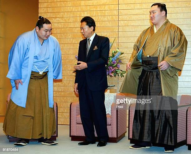 Mongolianborn sumo grand champions Asashoryu and Hakuho pose with Japanese Prime Minister Yukio Hatoyama during the courtesy visit at Hatoyama's...