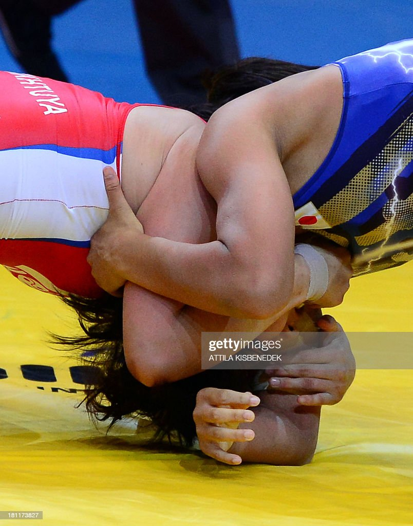 Mongolia's Munkhtuya Tungalag (red) and Japan's Ayaka Ito (blue) fight during the women's free style 59 kg category for bronze of the FILA World Wrestling Championships in Budapest on September 19, 2013. Tungalag won te bronze medal.
