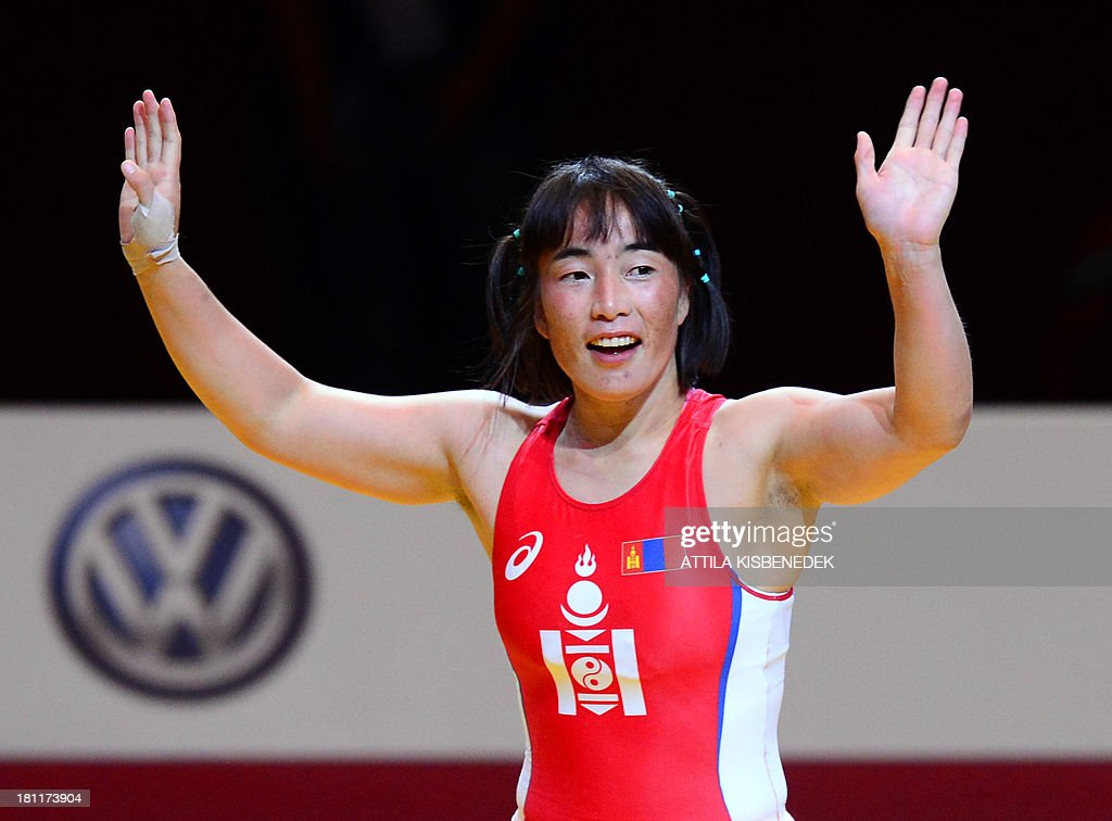 Mongolia's Munkhtuya Tungalag celebrates her victory over Japan's Ayaka Ito (not pictured) after the women's free style 59 kg category for bronze of the FILA World Wrestling Championships in Budapest on September 19, 2013. Tungalag won te bronze medal. AFP PHOTO / ATTILA KISBENEDEK