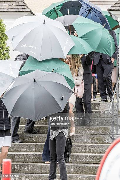 Monica Ivancan is shielded against the media and the rain with umbrellas as she leaves the church zum Hl Kreuz after her wedding with Christian Meier...