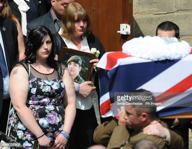 Monica Kershaw mother of Private Christopher Kershaw carries a white rose and a photograph of her son as she follows his coffin out of Holy Trinity...