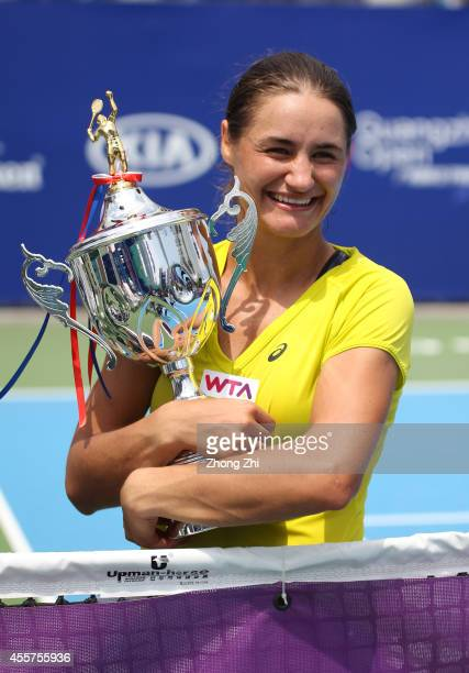 Monica Niculescu of Romania victorious with trophy after winning the final match against Alize Cornet of France on day six of the 2014 WTA Guangzhou...