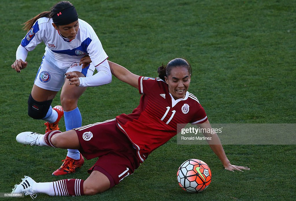 Monica Ocampo of Mexico falls in front of Laura Suarez of Puerto Rico during 2016 CONCACAF Women's Olympic Qualifying at Toyota Stadium on February...