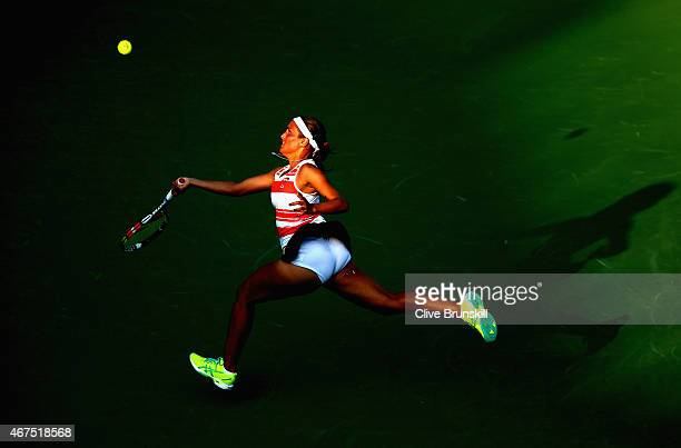 Monica Puig of Puerto Rico runs back down the court to return against Irina Falconi of the United States in their first round match during the Miami...